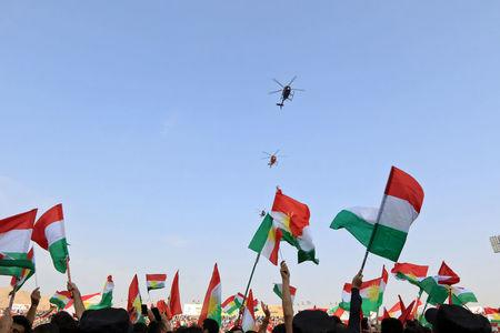 FILE PHOTO: Helicopters fly over Kurds who celebrate to show their support for the upcoming September 25th independence referendum in Duhuk