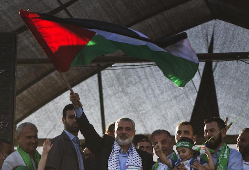 Hamas top leader in the Gaza Strip Ismail Haniya (C) waves the Palestinian national flag during a rally in Gaza City on August 27, 2014 (AFP Photo/Mahmud Hams)