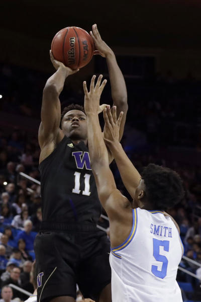 Washington guard Nahziah Carter, left, shoots over UCLA guard Chris Smith during the second half of an NCAA college basketball game in Los Angeles, Saturday, Feb. 15, 2020. (AP Photo/Chris Carlson)