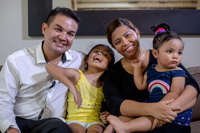 Bereaved parents Muhammad Reeza, 40, and Fazilah Kamaruddin, 37, pose in their Pasir Ris flat with two of their children Ely Aaryza, 8, and Eryn Falisha, one and a half. PHOTO: Dhany Osman/Yahoo News Singapore