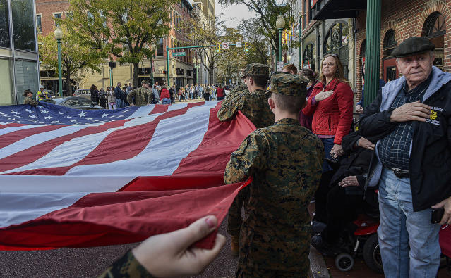 Parade goers in Charleston, WV salute a giant American flag as it is carried along Capitol Street on Nov. 11, 2019 during the Charleston Veterans Day parade. (Photo: F. Brian Ferguson/Charleston Gazette-Mail via AP)