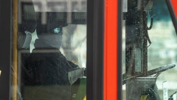 An OC Transpo driver wears a face covering while driving a bus on March 24, 2021. (Andrew Lee/CBC - image credit)