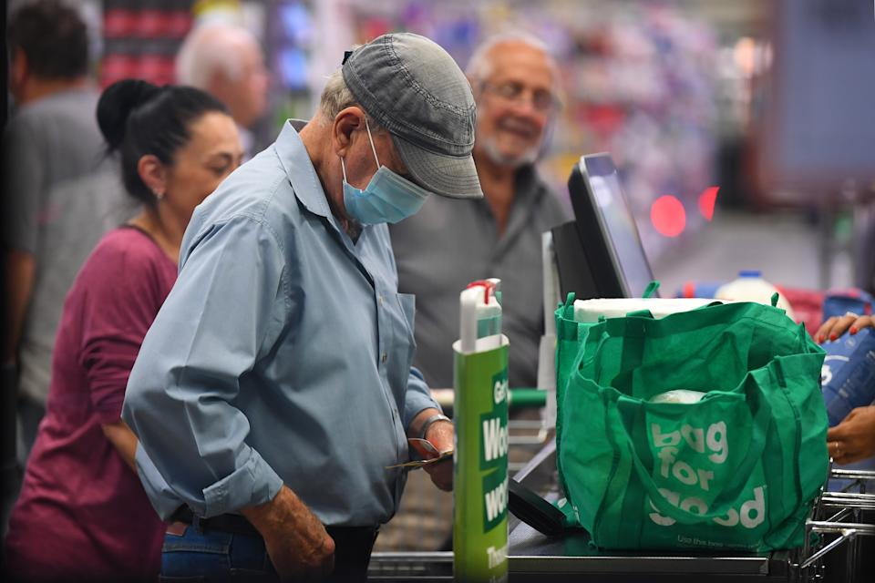A man wears a face mask as a preventative measure against corona virus at a checkout in a Woolworths supermarket.