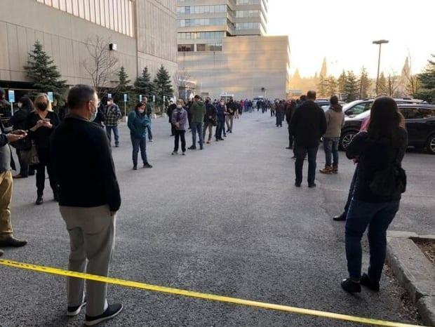 People wait in line to be vaccinated at the Palais des congrès in Gatineau, Que., on April 7, 2021.
