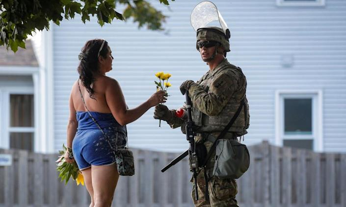 "<span class=""element-image__caption"">A woman hands flowers to a member of the Wisconsin national guard standing by as people gather for a vigil for Jacob Blake on Friday.</span> <span class=""element-image__credit"">Photograph: Brendan McDermid/Reuters</span>"