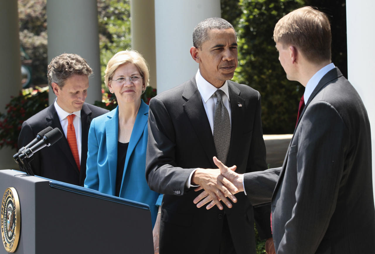President Barack Obama shakes hands with former Ohio Attorney General Richard Cordray, right, after announcing the nomination of Cordray to serve as the first director of the Consumer Financial Protection Bureau (CFPB), Monday, July 18, 2011, in the Rose Garden of the White House in Washington. Treasury Secretary Timothy Geithner is at left, and Elizabeth Warren, head the Consumer Financial Protection Bureau, is second from left. (AP Photo/Pablo Martinez Monsivais)