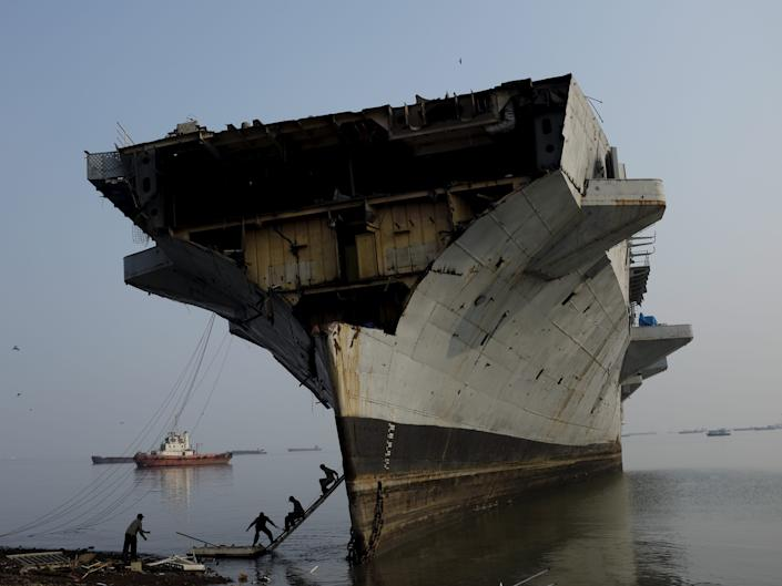 Workers climb down from decommissioned Indian Navy Ship INS Vikrant at a ship breaking yard in Mumbai Workers climb down from decommissioned Indian Navy Ship INS Vikrant at a ship breaking yard in Mumbai, India, November 24, 2014.