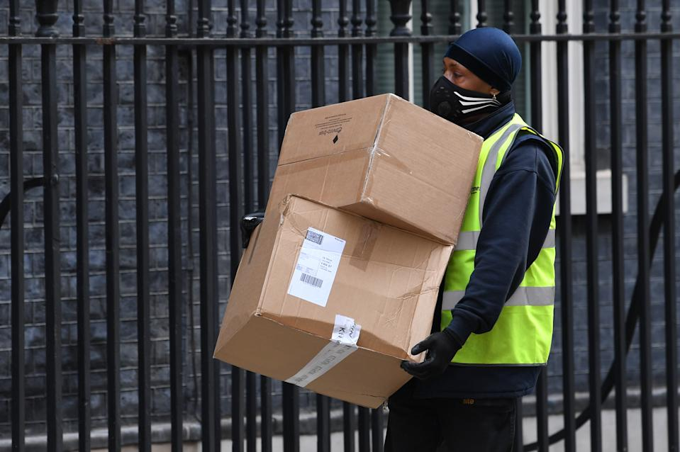 A delivery man carries a Kit & Kin boxe into Downing Street. (PA)