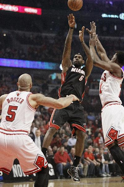 Miami Heat small forward LeBron James (6) shoots against Chicago Bulls small forward Jimmy Butler, right and Chicago Bulls power forward Carlos Boozer (5) during the first half of Game 3 of an NBA basketball playoffs Eastern Conference semifinal on Friday, May 10, 2013, in Chicago. (AP Photo/Charles Rex Arbogast)