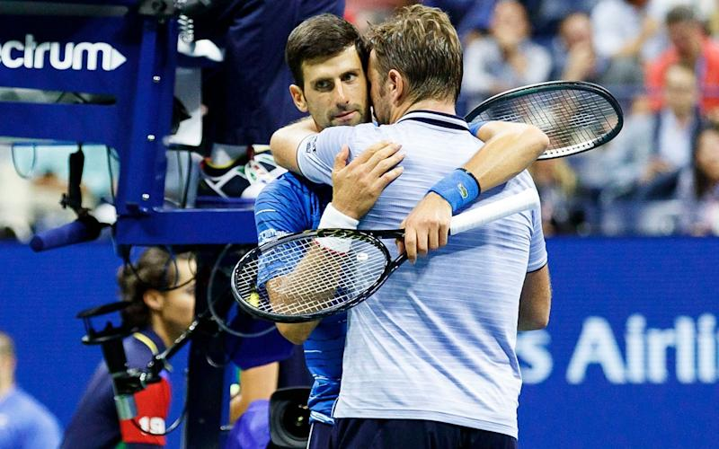 Novak Djokovic and Stan Wawrinka (R) embrace at the end of their fourth-round match - REX