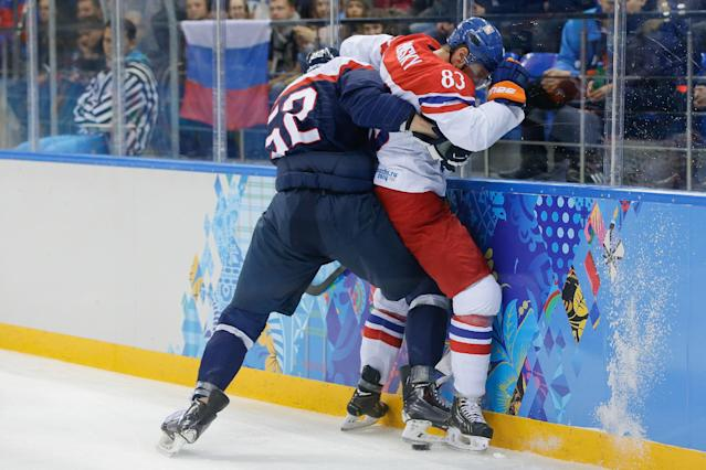 Slovakia defenseman Martin Marincin pins Czech Republic forward Ales Hemsky against the boards as they fight for control of the puck during the first period of the 2014 Winter Olympics men's ice hockey game at Shayba Arena, Tuesday, Feb. 18, 2014, in Sochi, Russia. (AP Photo/Matt Slocum)