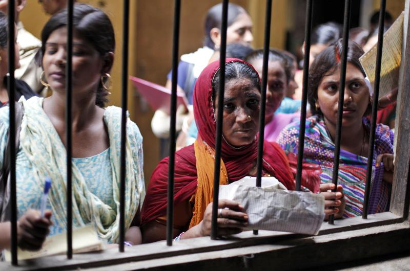 In this Wednesday, Aug. 29, 2012 photo, Unemployed educated Indian women wait to register themselves at the Employment Exchange Office in Allahabad, India. India, with the world's largest chunk of illiterates at over 250 million, has to invest heavily in education and skills training, said Ashish Bose, a leading demographer. While millions of job seekers have impressive sounding diplomas, many don't have the skills promised by those certificates from colleges and technical institutes with poor standards. (AP Photo/Rajesh Kumar Singh)
