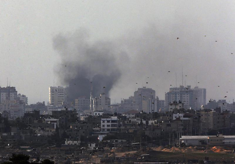 Birds fly as a plume of smoke is seen over central Gaza Strip, after an airstrike by Israeli forces, as seen from the Israel Gaza border, Monday, Nov. 19, 2012. Israeli aircraft struck crowded areas in the Gaza Strip and killed a senior militant with a missile strike on a media center Monday, driving up the Palestinian death toll to 96, as Israel broadened its targets in the 6-day-old offensive meant to quell Hamas rocket fire on Israel. (AP Photo/Lefteris Pitarakis)