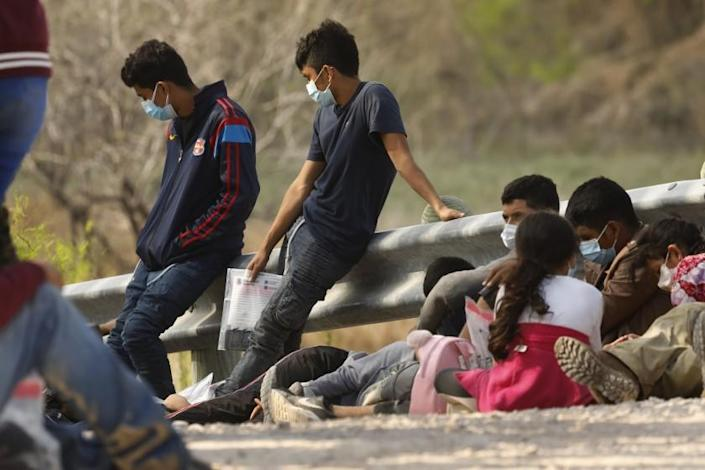 MISSION, TEXAS -Asylum seekers who crossed the U.S. - Mexico border illegally wait to be processed outside Mission, Texas on March 17, 2020: Wednesday, March 17, 2021 in Mission, Texas. (Carolyn Cole / Los Angeles Times)