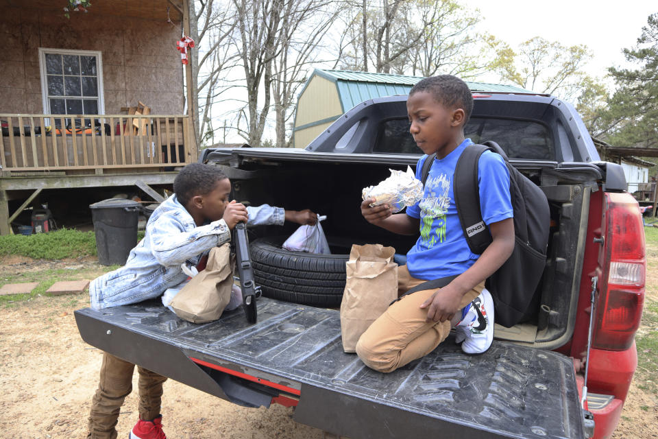 Kejuan Turner, 8, eats a burger from a free bagged lunch provided by the Jefferson County School District on the back of his mother's truck with his brother, Kendrell, 9, outside their home in Fayette, Miss., on Monday, March 22, 2021. The children receive the meals while at daycare and eat them at when they get home in the afternoons. (AP Photo/Leah Willingham)