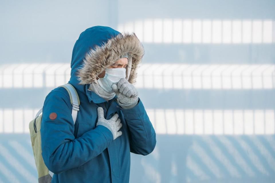 Portrait of sick young man in blue jacket put on a hood, having a cold, feeling unwell, coughing, wearing medical face mask, outdoors