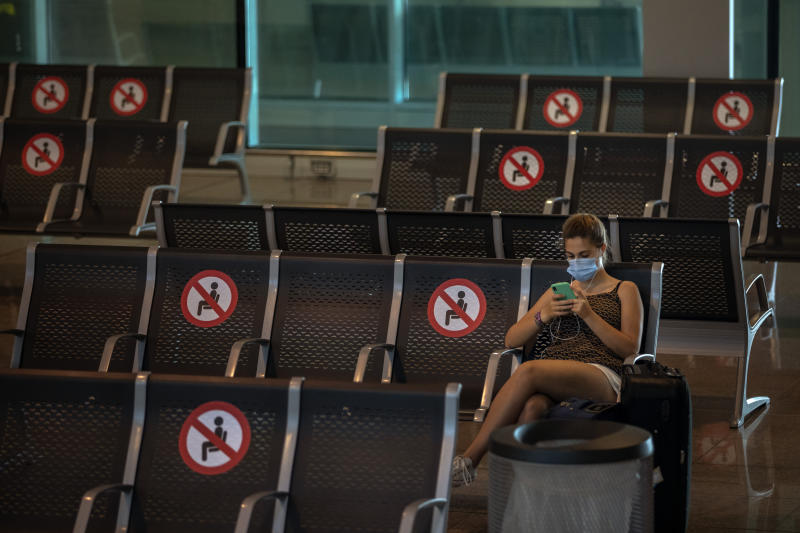 A passenger sits at Barcelona airport in Barcelona, Spain, Tuesday, June 30, 2020. The European Union on Tuesday is announcing a list of nations whose citizens will be allowed to enter 31 European countries. As Europe's economies reel from the impact of the coronavirus, southern EU countries like Greece, Italy and Spain are desperate to entice back sun-loving visitors and breathe life into their damaged tourism industries. (AP Photo/Emilio Morenatti)