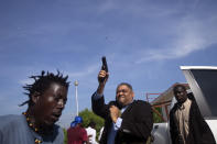 Opposition Senator Ralph Fethiere fires his gun outside Parliament as he arrives for a ceremony to ratify Fritz William Michel's nomination as prime minister in Port-au-Prince, Haiti, Sept. 23, 2019. Opposition members confronted ruling-party senators, and Fethiere pulled a pistol when protesters rushed at him and members of his entourage. The image was part of a series of photographs by Associated Press photographers which was named a finalist for the 2020 Pulitzer Prize for Breaking News Photography. (AP Photo/Dieu Nalio Chery)