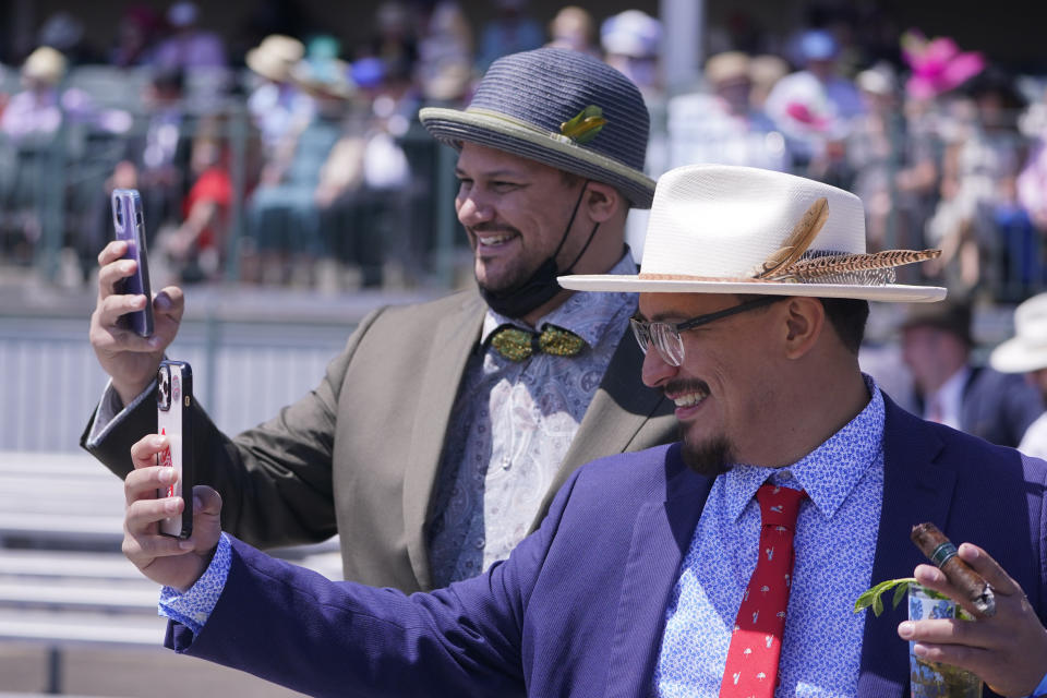 Men take photos of themselves before the 147th running of the Kentucky Derby at Churchill Downs, Saturday, May 1, 2021, in Louisville, Ky. (AP Photo/Michael Conroy)