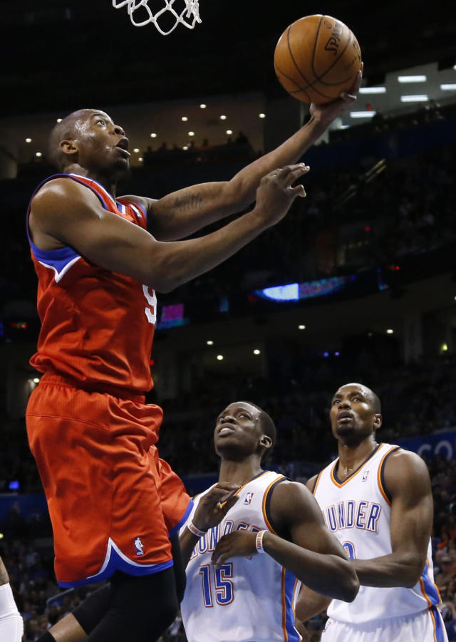 Philadelphia 76ers guard James Anderson (9) shoots in front of Oklahoma City Thunder guard Reggie Jackson (15) and forward Serge Ibaka during the first quarter of an NBA basketball game in Oklahoma City, Tuesday, March 4, 2014. (AP Photo/Sue Ogrocki)