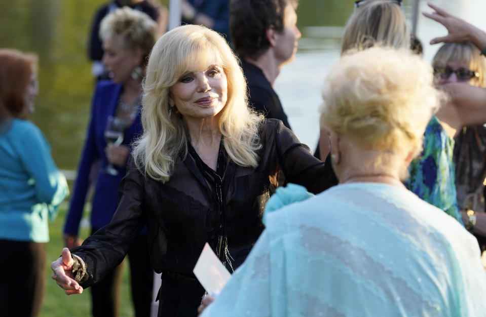 Actress Loni Anderson, the former wife of the late actor Burt Reynolds, greets actress Ruta Lee, foreground, at the unveiling of a memorial sculpture of Reynolds at Hollywood Forever Cemetery, Monday, Sept. 20, 2021, in Los Angeles. Reynolds died in 2018 at the age of 82. (AP Photo/Chris Pizzello)