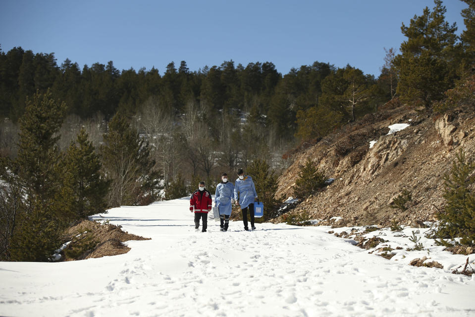 Dr. Rustem Hasbek, Dr. Yasin Kaya and health worker Yusuf Duran, of the Koyulhisar Public Health Center vaccination team, walk to vaccinate residents in the isolated village of Gumuslu in the district of Sivas, central Turkey, Friday, Feb. 26, 2021. (AP Photo/Emrah Gurel)