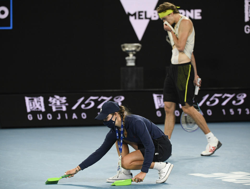 A ball girl sweeps up debris after Serbia's Novak Djokovic smashed his racket during his quarterfinal against Germany's Alexander Zverev at the Australian Open tennis championship in Melbourne, Australia, Tuesday, Feb. 16, 2021.(AP Photo/Andy Brownbill)