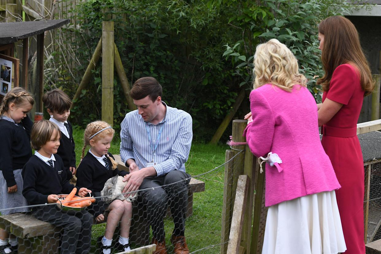 Britain's Catherine, Duchess of Cambridge and US First Lady Jill Biden chat with children feeding a rabbit during their visit to Connor Downs Academy in Hayle, Cornwall on the sidelines of the G7 summit on June 11, 2021. (Photo by DANIEL LEAL-OLIVAS / POOL / AFP) (Photo by DANIEL LEAL-OLIVAS/POOL/AFP via Getty Images)
