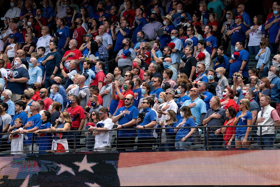 Fans stand for the national anthem before a baseball game between the Texas Rangers and the Toronto Blue Jays on April 5, 2021, in Arlington, Texas.