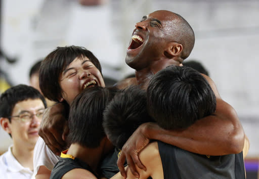 NBA's Los Angeles Lakers Kobe Bryant embraces South Korean students in his basketball clinic for youth in Seoul, South Korea, Thursday, July 14, 2011. Bryant is in Seoul during his five-Asian cities tour. (AP Photo/Lee Jin-man)