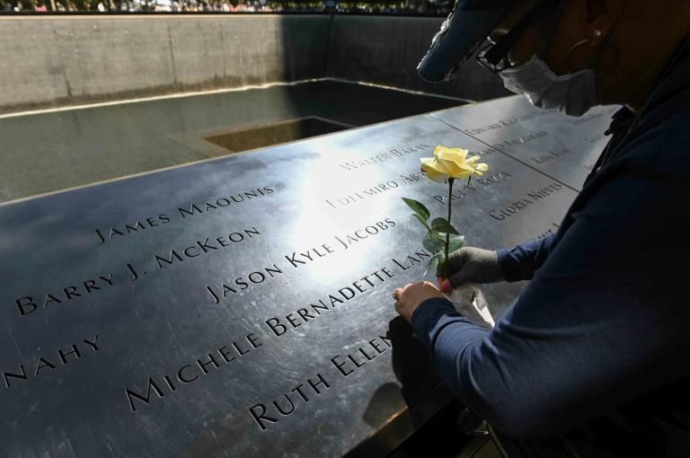 Linda Terry places a flower near the name of a friend and former client, who died on 9/11 at the National 9/11 Memorial & Museum on September 10, 2021 (AFP/ROBERTO SCHMIDT)