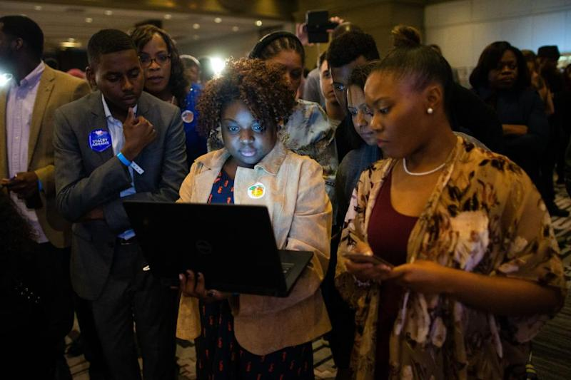 Attendees look at a laptop computer during an election night watch party for Stacey Abrams, Democratic nominee for governor of Georgia, not pictured, in Atlanta, Georgia, U.S., on Tuesday, Nov. 6, 2018.