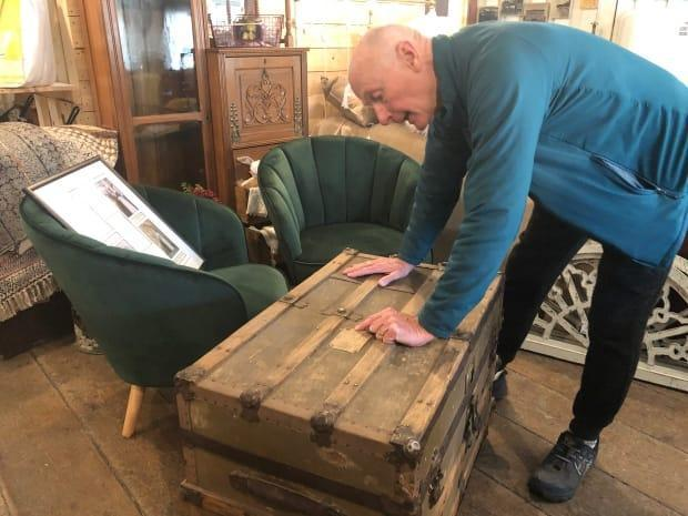 Ted Staffen of Whitehorse with an old trunk that used to belong to his family in Saskatchewan. The trunk recently turned up at a Whitehorse antique shop. (Elyn Jones/CBC - image credit)