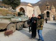 The monastery's abbot Father Hovhannes walks past a military vehicle of the Russian peacekeeping forces at Dadivank monastery in Kalbajar district