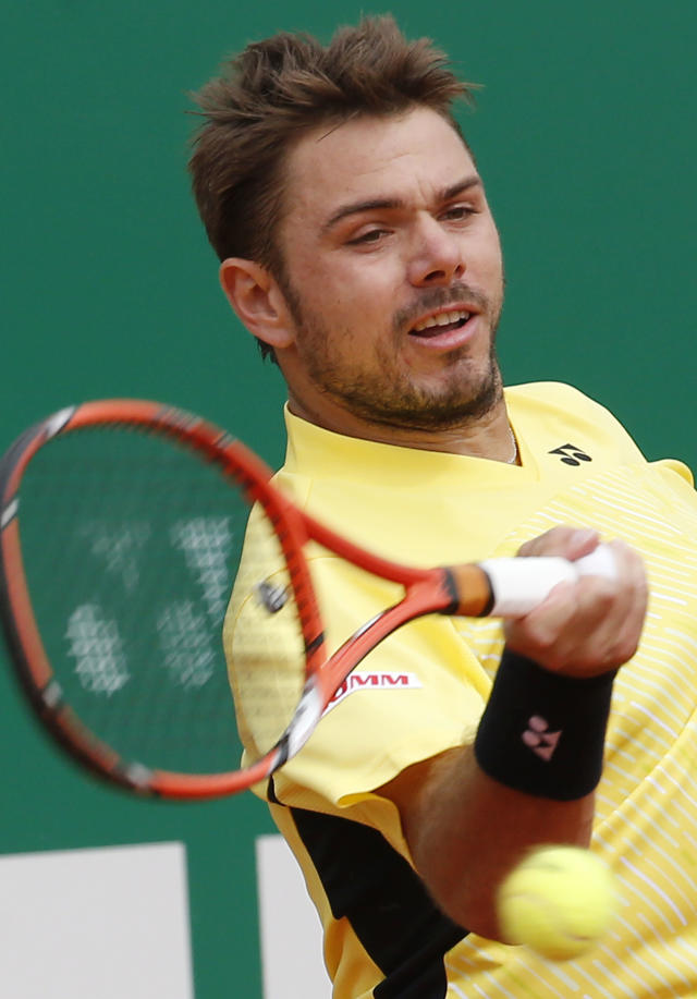 Stanislas Wawrinka of Switzerland returns to the ball to Milos Raonic of Canada during their quarterfinals match of the Monte Carlo Tennis Masters tournament in Monaco, Friday, April 18, 2014. Wawrinka won 7-6 6-2. (AP Photo/Michel Euler)