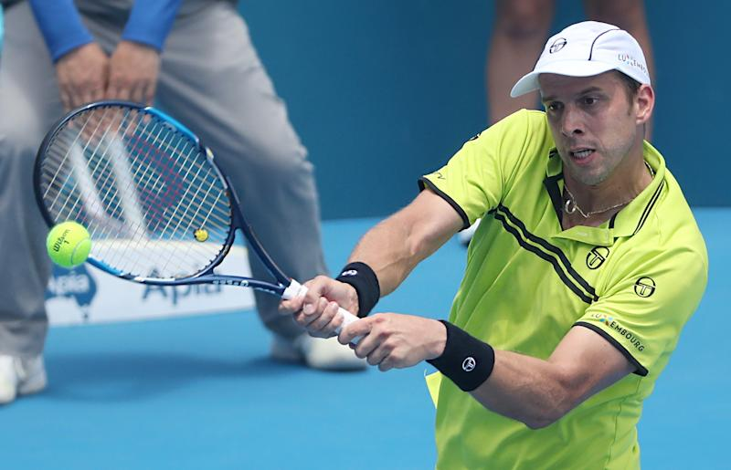 Gilles Muller of Luxembourg hits a return to Pablo Cuevas of Uruguay in their men's quarter-final match at the Sydney International tennis tournament, on January 12, 2017 (AFP Photo/Glenn Nicholls)