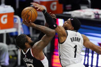 Los Angeles Clippers guard Paul George, left, shoots as Brooklyn Nets guard Bruce Brown defends during the second half of an NBA basketball game Sunday, Feb. 21, 2021, in Los Angeles. (AP Photo/Mark J. Terrill)
