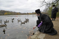 Garbed in traditional clothing worn by some Orthodox Jews, Zvi Kurtz offers food to resident geese and a mallard as the waterfowl swim in Prospect Lake in Prospect Park, Sunday, Nov. 15, 2020, in the Brooklyn borough of New York. (AP Photo/Kathy Willens)