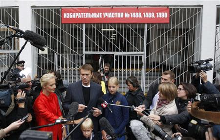 Russian opposition leader Alexei Navalny (C), accompanied by his wife Yulia and children Dasha and Zakhar, talks to the media outside a polling station in Moscow September 8, 2013. REUTERS/Maxim Shemetov