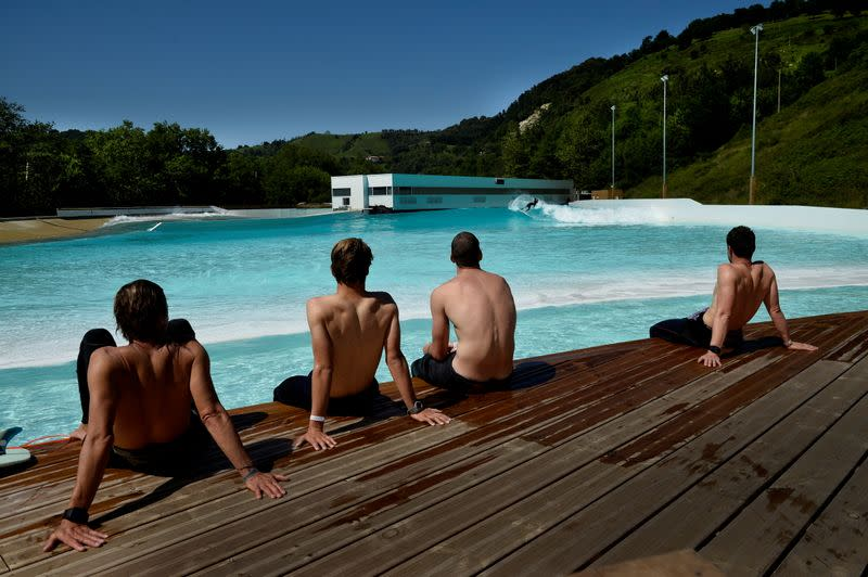 FILE PHOTO: Members of Germany's national surf team watch surfers ride in Wave Garden, a giant pool that generates surfable waves, in the Basque town of Aizarnabazaba