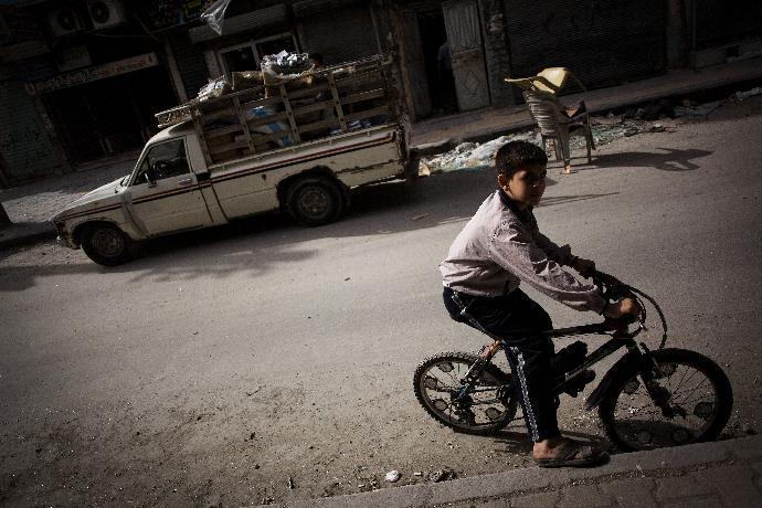 In this Saturday, Oct. 20, 2012 photo, a Syrian boy rides his bike in Karma Jabl district in Aleppo, Syria. With death lurking around every corner, the survival instincts of Aleppo's population are being stretched to the limit every day as the battle between Syria's rebels and the regime of President Bashar Assad for the country's largest city stretches through its fourth destructive month. Residents in the rebel-held neighborhoods suffering the war's brunt tell tales of lives filled with fear over the war in their streets, along with an ingenuity and resilience in trying to keep their shattered families going. (AP Photo/ Manu Brabo)