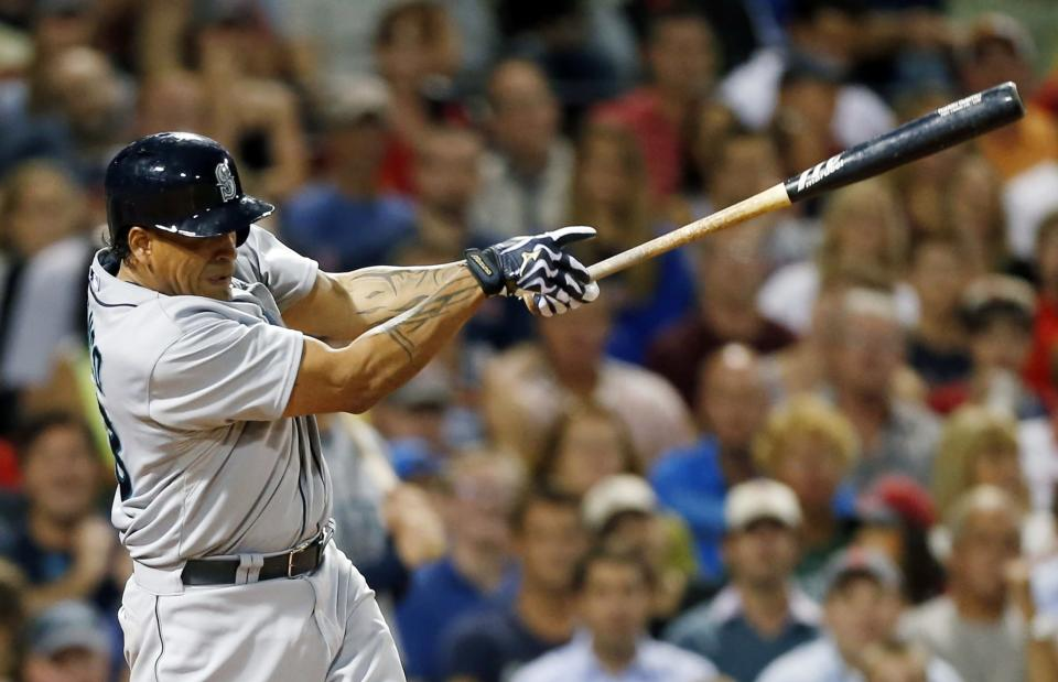 Seattle Mariners' Henry Blanco follows through on a grand slam in the fifth inning of a baseball game against the Boston Red Sox in Boston, Thursday, Aug. 1, 2013. (AP Photo/Michael Dwyer)