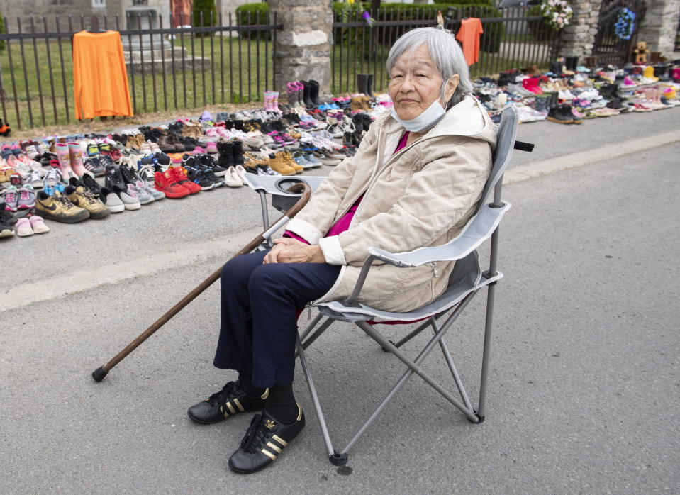 Residential school survivor Betty Deer sits next to children's shoes, placed there as a tribute to the victims of the residential school system outside St. Francis Xavier Church in Kahnawake, Quebec, Sunday, May 30, 2021. The remains of 215 children, some as young as 3 years old, have been found buried on the site of what was once Canada's largest Indigenous residential school — one of the institutions that held children taken from families across the nation. (Graham Hughes/The Canadian Press via AP)