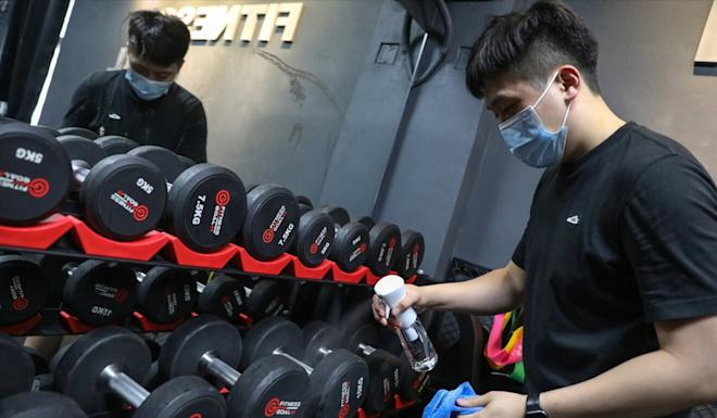 A staff member at a gym in Mong Kok cleans equipment on Wednesday in anticipation of reopening amid a new round of relaxed social-distancing measures. Photo: Nora Tam