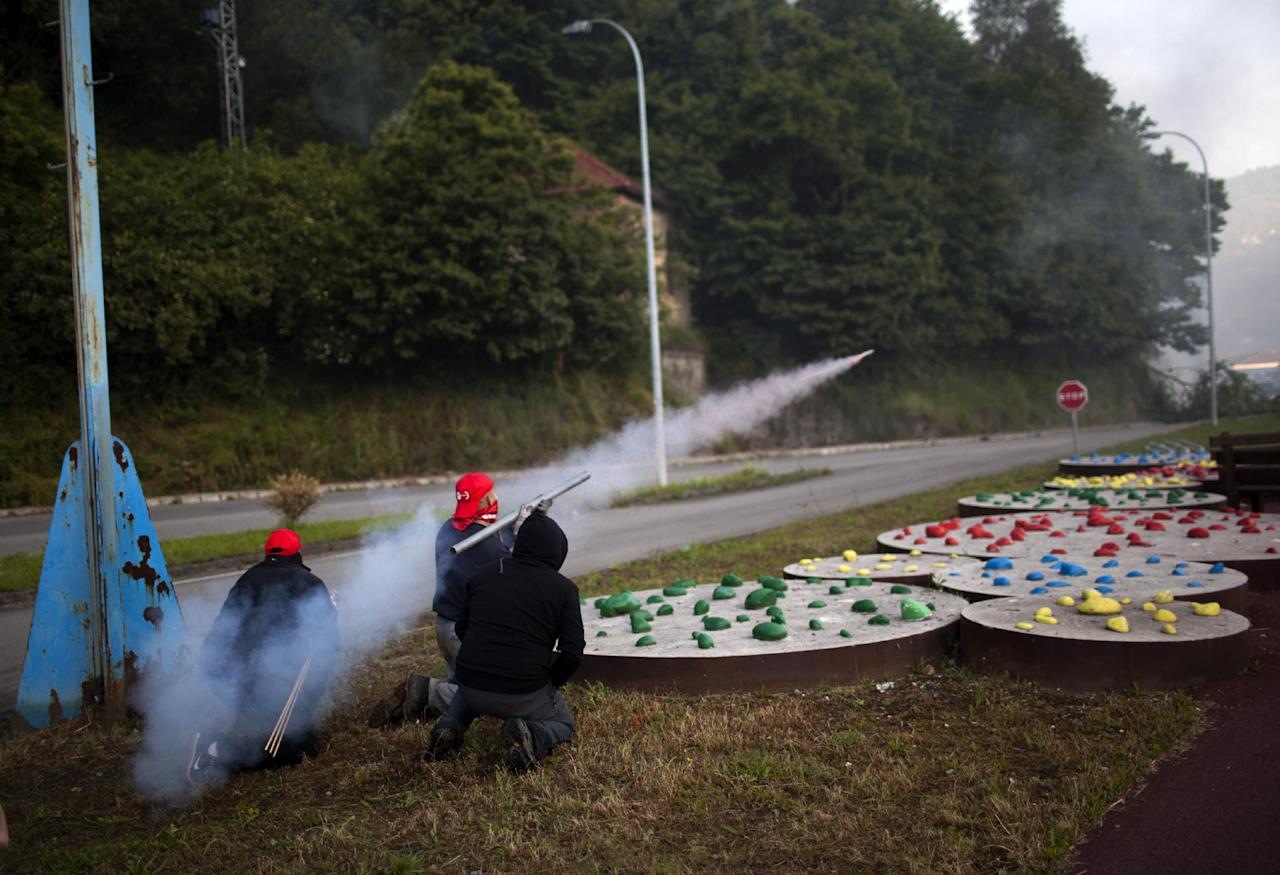 """Miners fire handmade rockets at riot police officers as they defend their position near the mine """"El Soton"""" during clashes in El Entrego near Oviedo, Spain, Friday, June 15, 2012. Strikes, road blockades, and mine sit-ins continue as 8,000 mineworkers at over 40 coal mines in northern Spain continue their protests against government action to cut coal subsidies. (AP Photo/Emilio Morenatti)"""