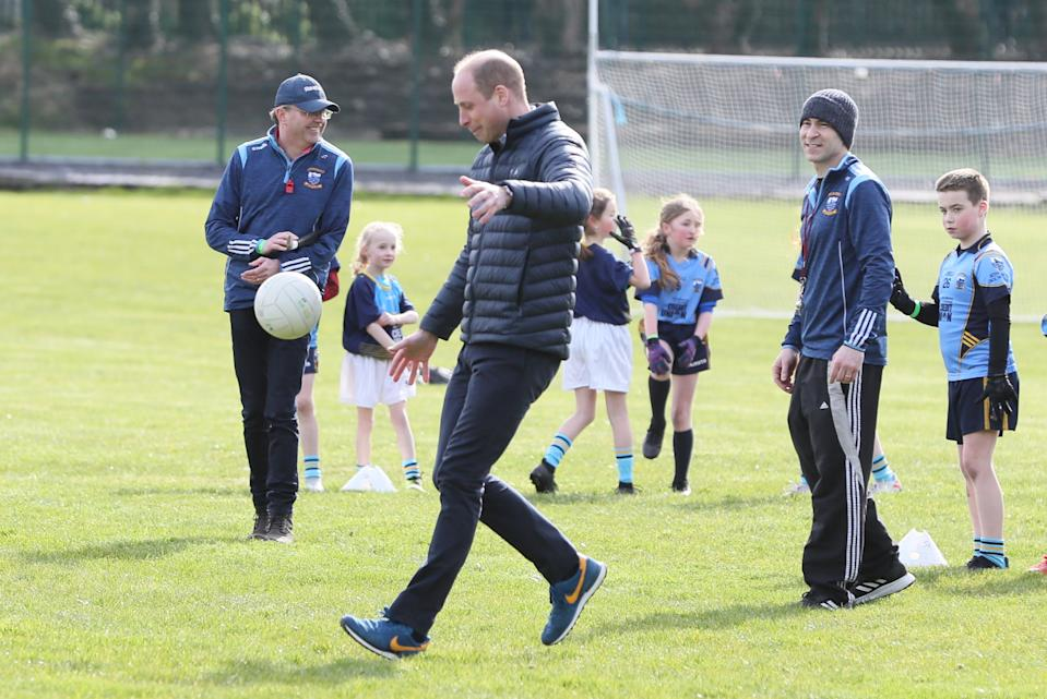 The Duke of Cambridge tries out Gaelic football during a visit to a local Gaelic Athletic Association (GAA) club to learn more about traditional sports during the third day of their visit to the Republic of Ireland.