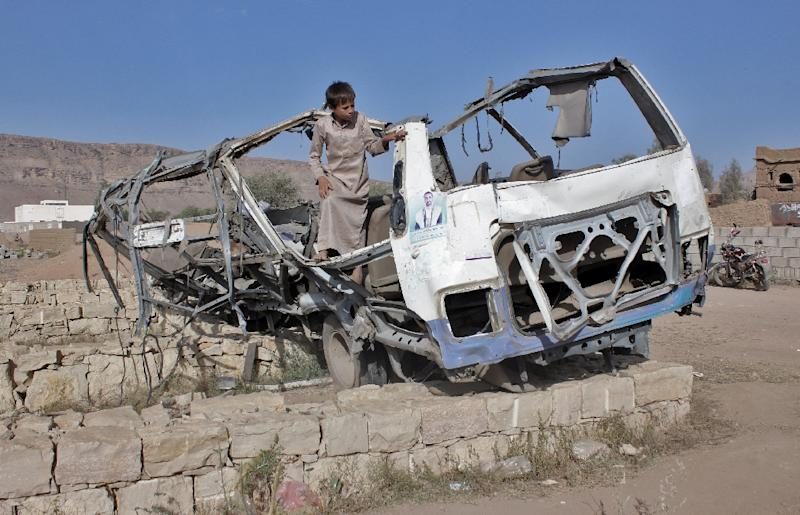 A Yemeni boy on September 4, 2018 stands in the wreckage of the bus which was hit by a Saudi-led coalition air strike (AFP Photo/STRINGER)
