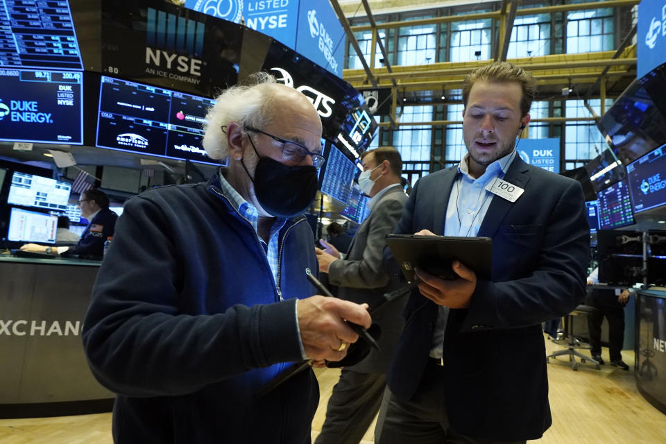 Trader Peter Tuchman, left, and Benjamin Tuchman, father and son, work on the floor of the New York Stock Exchange, Monday, July 12, 2021. Stocks are wobbling between small gains and losses in the early going on Wall Street Monday as investors look ahead to a wave of earnings reports from big U.S. companies coming out this week. (AP Photo/Richard Drew)