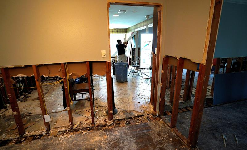 A man tears out damaged parts of a home.