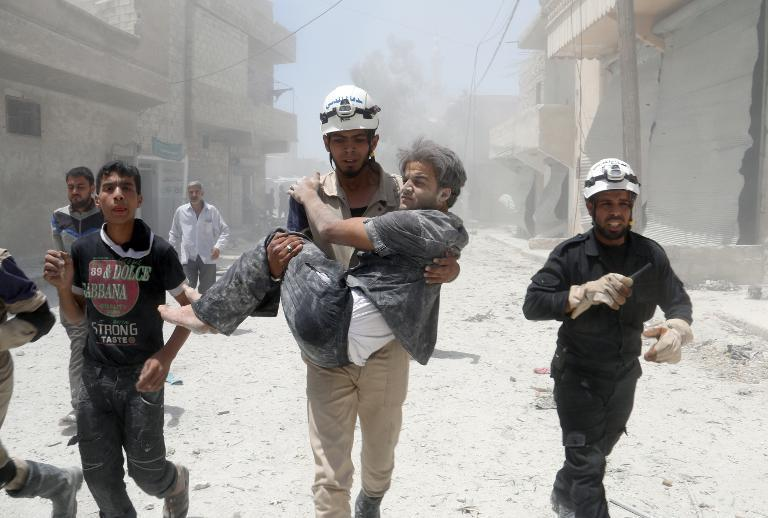 A Syrian rescue worker carries a man following an alleged airstrike by a Syrian army helicopter in the northern city of Aleppo, on June 11, 2014